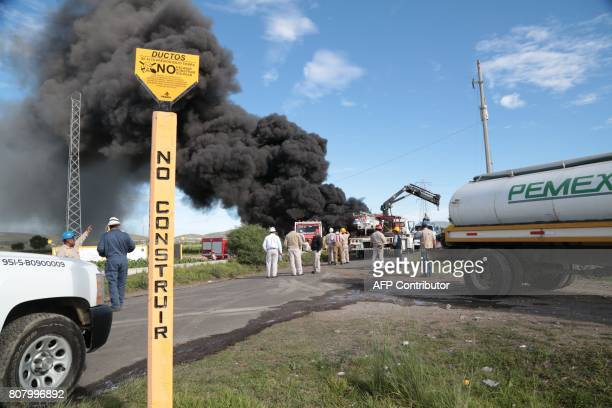 Workers of the Mexican stateowned oil company Pemex and local firefighters work to control a fire believed to have started in the pipe due to...
