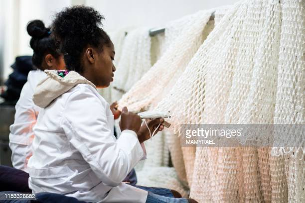Workers of the Rova Caviar Madagascar company prepare the nets at the Acipenser factory on June 4 2019 in Mantasoa Madagascar for the fishing of the...