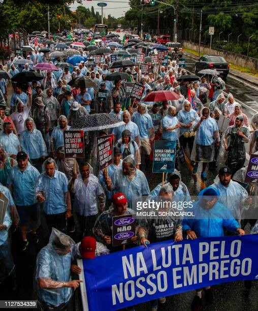 Workers of US automaker Ford hold a banner reading Fighting for our job during a protest against the closure of the plant in Sao Bernardo do Campo...