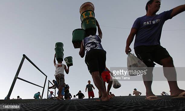 Workers offload baskets of acai berry at sunrise at the historic VeroPeso market on June 6 2012 in Belem Brazil Belem is considered the entrance gate...