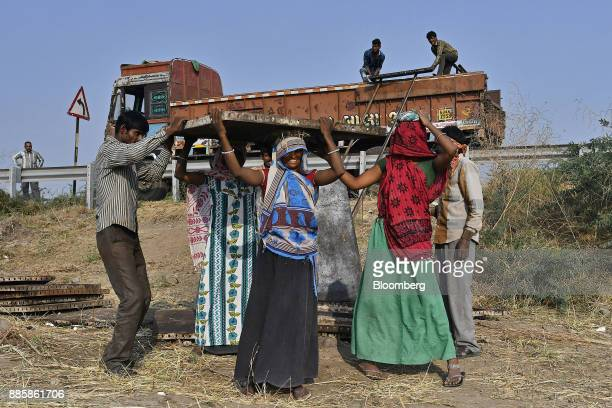 Workers offload building materials from a truck on a project site for a 920squarekilometer industrial area located on the DelhiMumbai Industrial...