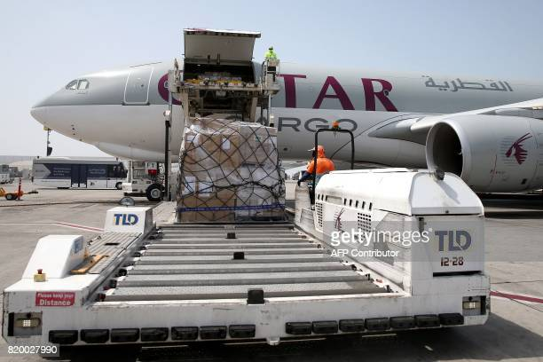 Workers offload cargo from a Qatar Airways Cargo plane at the Hamad International Airport in Doha on July 20 2017 / AFP PHOTO / STRINGER
