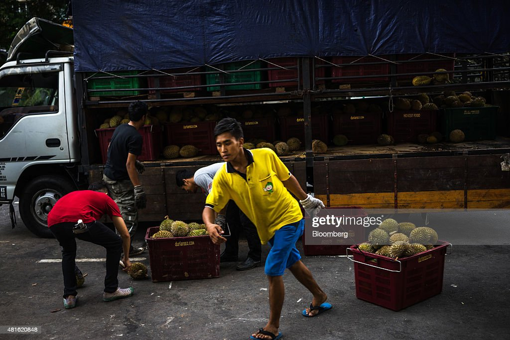 Workers offload crates of durians from a truck at a vendor's road side stall in Petaling Jaya, Selangor, Malaysia, on Monday, July 13, 2015. The Southeast Asian native fruit -- known for its sweet, custardy flesh and banned from Singapore's subways and hotels because of its pungent odor -- can retail for more than S$40 ($30) apiece in Singapore. Photographer: Sanjit Das/Bloomberg via Getty Images