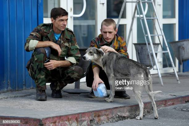 Workers on a break pet a stray dog they have named Bulka outside an administrative building inside the exclusion zone at the Chernobyl nuclear power...