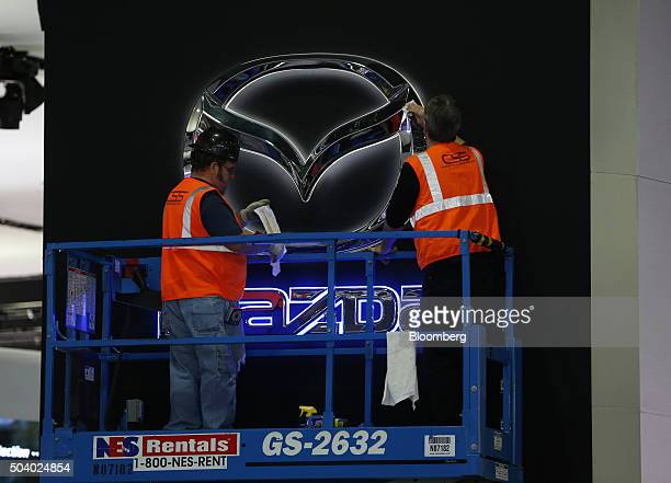 Workers on a hydraulic lift polish a Mazda Motor Corp logo at the company's exhibit ahead of the North American International Auto Show at the Cobo...