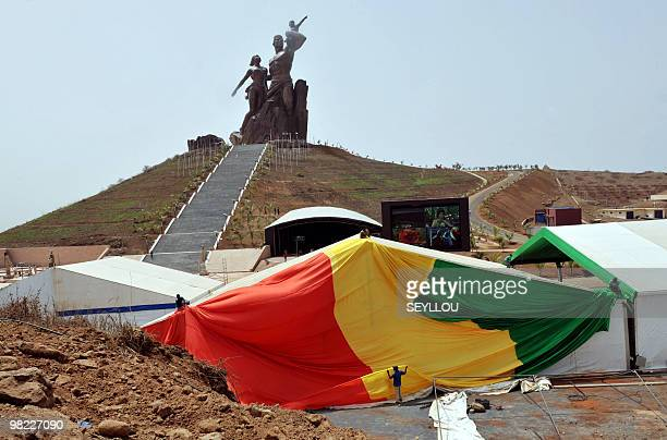 Workers on April 1 2010 put up the Senegalese national flag in preparations for the inauguration on April 3 where heads of states shall be arriving...