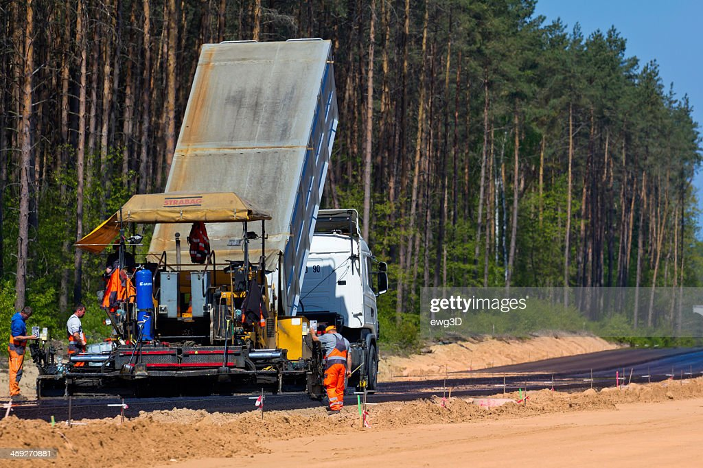 workers on asphalting paver machine during highway repairing stock photo