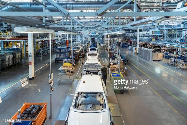 workers on car production line in car factory - fließbandfertigung stock-fotos und bilder
