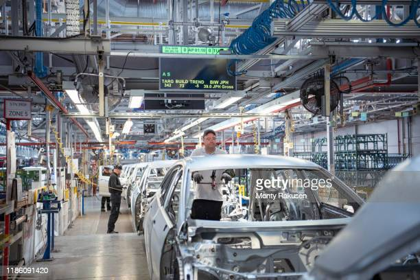 workers on car production line in car factory - monty rakusen stock pictures, royalty-free photos & images