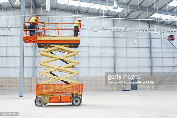 Workers on cherry picker on site