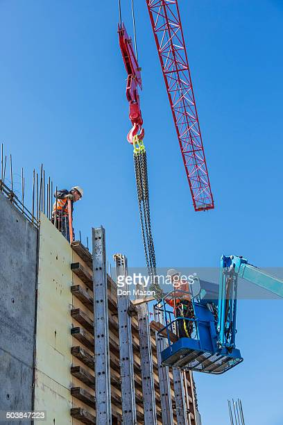 Workers on concrete wall form on construction site