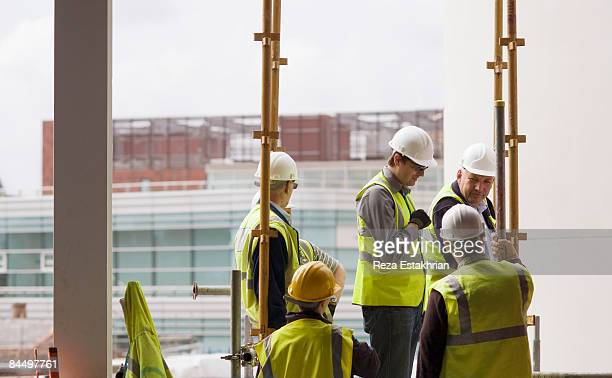 workers on construction site discuss. - industry stock pictures, royalty-free photos & images