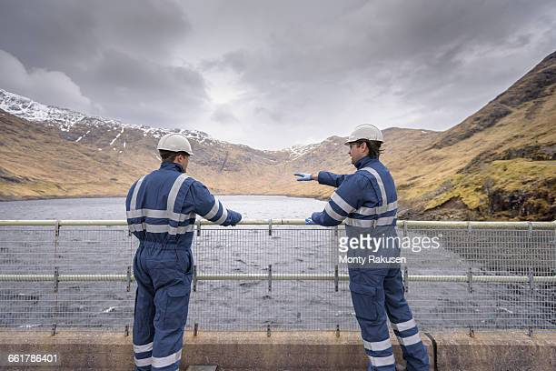 workers on dam with water at hydroelectric power station - reservoir stock pictures, royalty-free photos & images