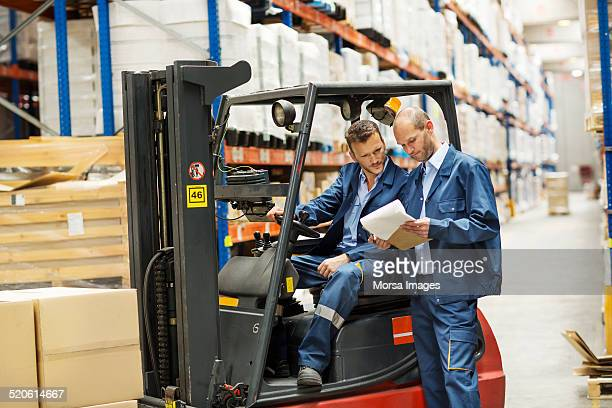 Workers on forklift discussing at warehouse