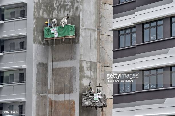 Workers on gondolas apply cement plastering on a newly constructed public housing building in Singapore on December 9 2017 / AFP PHOTO / ROSLAN RAHMAN