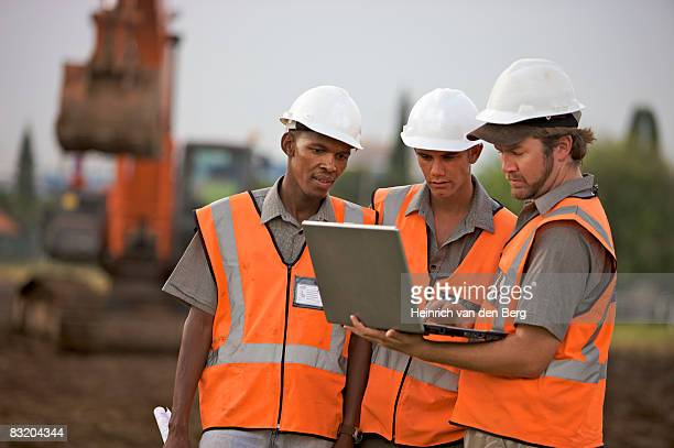 Workers on laptop at construction site. Johannesburg, Gauteng Province, South Africa