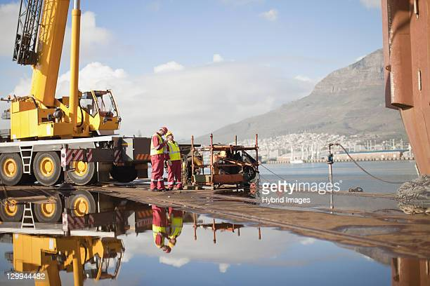 Workers on oil rig standing by crane