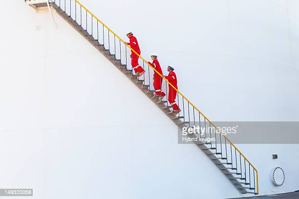 workers on steps at chemical plant - gas refinery stock photos and pictures