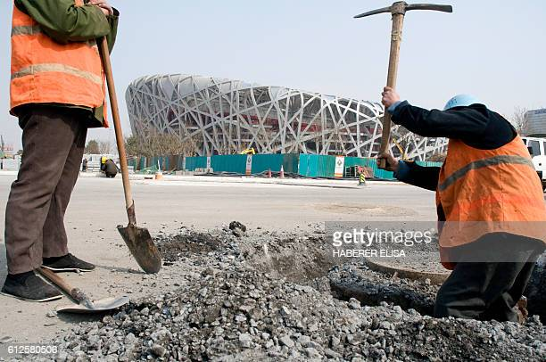 Workers on the construction site of the National Olympic Stadium also known as the Bird's Nest The stadium will host athletics competitions and the...