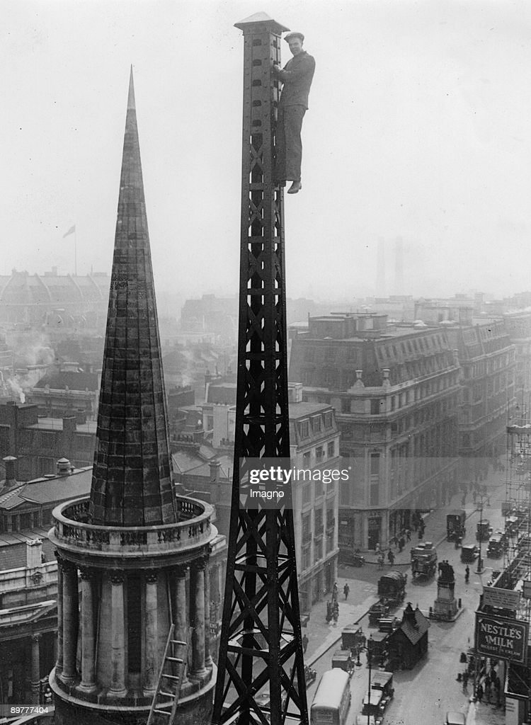 Workers on the transmitter mast of the new building of BBC in London, Langham Place. The steeple belongs to the All Souls Church. Photograph. England. April 30th 1931.