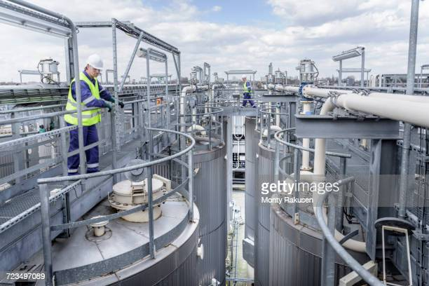 Workers on top of process plant in oil blending factory