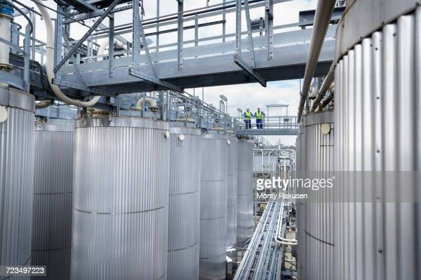 workers on top of process plant in oil blending factory - monty rakusen stock pictures, royalty-free photos & images