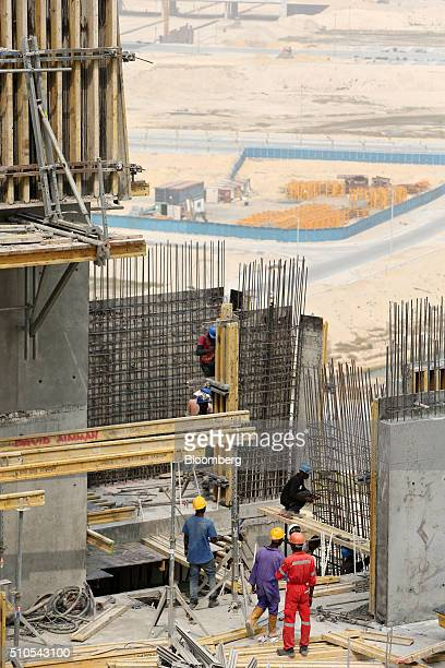 Workers operate among reinforcement rods during the construction of walls on the upper levels of a tower block at the Eko Atlantic city site,...