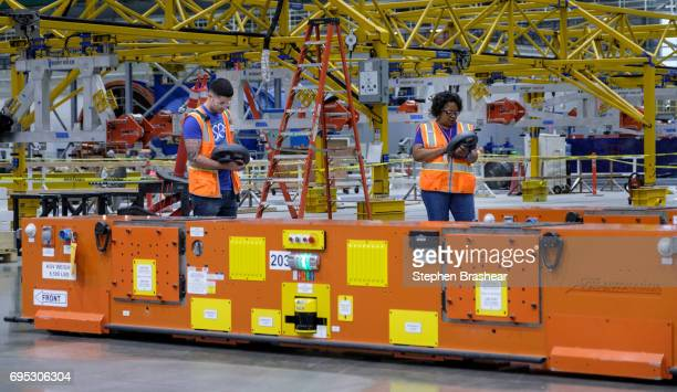 Workers operate an automated guided vehicle carrying a wing part through the Boeing 777X Composite Wing Center on June 12 2017 in Everett Washington...