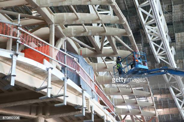 Workers operate from an aerial platform near the passenger departures hall entrance at Abu Dhabi airport's MidField terminal during construction in...