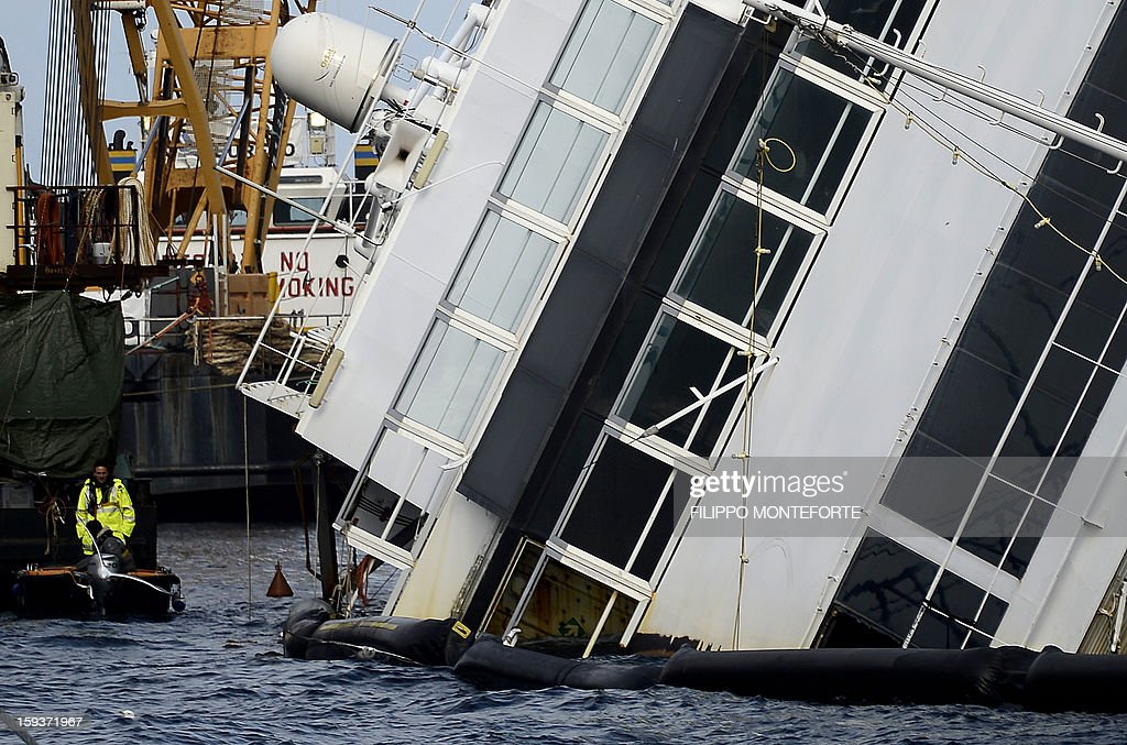 Workers operate in front of the Costa Concordia cruise ship laying aground by the port the Italian island of Giglio on January 12, 2013. A year on from the Costa Concordia tragedy in which 32 people lost their lives, the giant cruise ship still lies keeled over on an Italian island and its captain Francesco Schettino has become a global figure of mockery.
