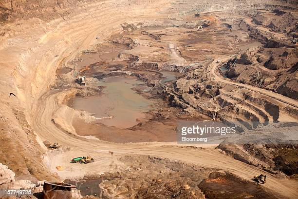 Workers operate mining excavators to extract ore from the open pit at Katanga Mining Ltd's KOV coppercobalt mine in Kolwezi Katanga province...