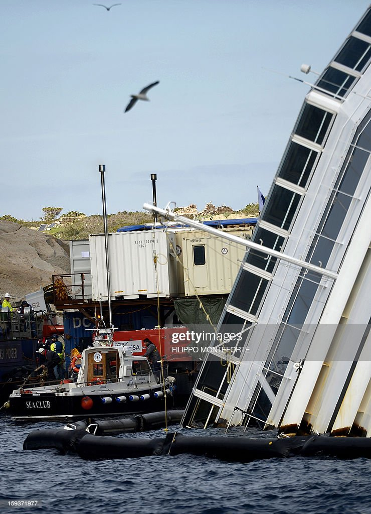 Workers operate near the Costa Concordia cruise ship laying aground outside the port the western Italian island of Giglio on January 12, 2013. A year after the Costa Concordia tragedy in which 32 people lost their lives, the giant cruise ship still lies keeled over on an Italian island and its captain Francesco Schettino has become a global figure of mockery.