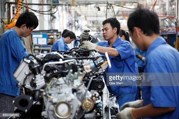 Workers operate on the assembly line at the SAIC GM Wuling Automobile Co Ltd factory in Liuzhou Guangxi Province China on August 24 2009 The Wuling...