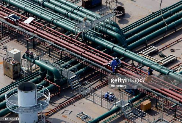 Workers operate on the deck of an almostcompleted oil tanker at the Dalian shipyard in Dalian Liaonin Province China on Saturday April 23 2011...
