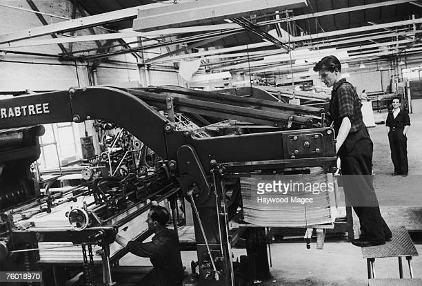 Workers operating a machine printing or preparing labels for Weston's biscuits at a Clydeside factory 20th August 1955 Original Publication Picture...