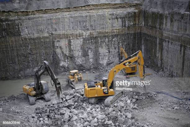 Workers operating Caterpillar Inc equipment dig a foundation for a hotel during construction in Nashville Tennessee US on Wednesday Oct 2 2017...