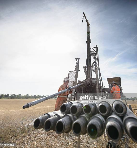 workers operating drilling rig in field - モーペス ストックフォトと画像