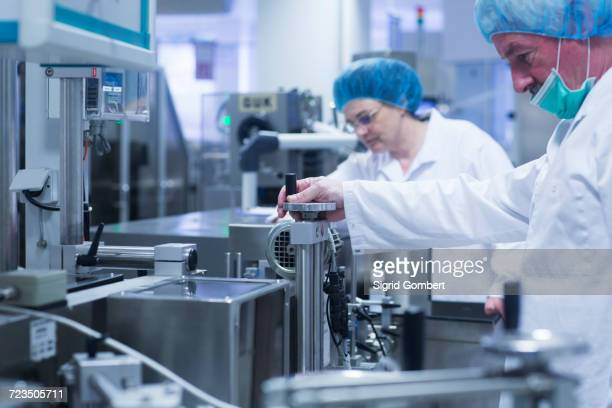 workers operating machinery in pharmaceutical plant - sigrid gombert stock pictures, royalty-free photos & images
