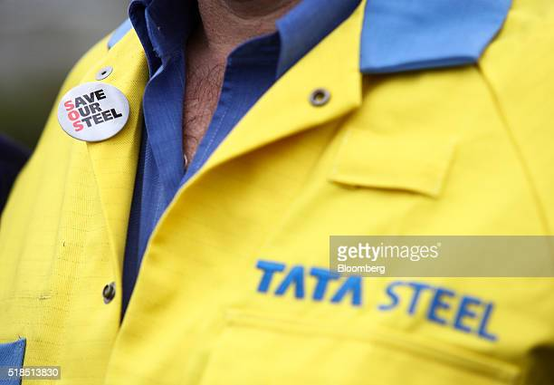 Worker's overalls displays a 'save our steel' badge as he stands outside the main entrance to the steel works operated by Tata Steel Ltd. In Port...