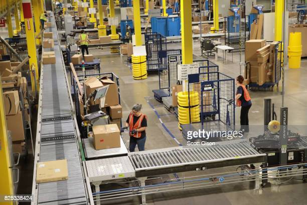 Workers pack and ship customer orders at the 750000squarefoot Amazon fulfillment center on August 1 2017 in Romeoville Illinois On August 2 Amazon...