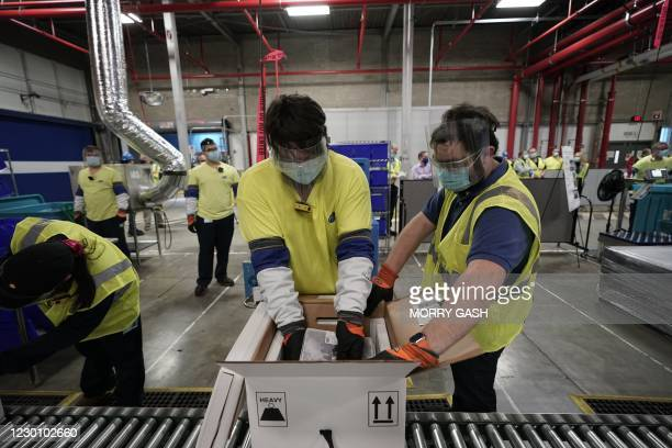 Workers pack boxes containing the Pfizer-BioNTech Covid-19 vaccine as they are prepared to be shipped at the Pfizer Global Supply Kalamazoo...