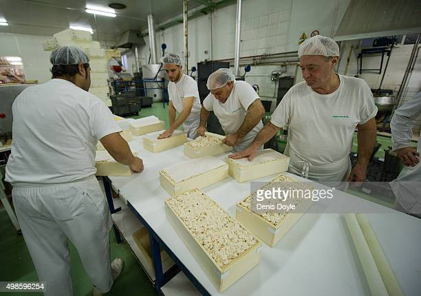 Workers pack freshly made 'Turron de Alicante' a variety of turron at the El Abuelo artisan factory on November 24 2015 in Jijona Spain Turron is...