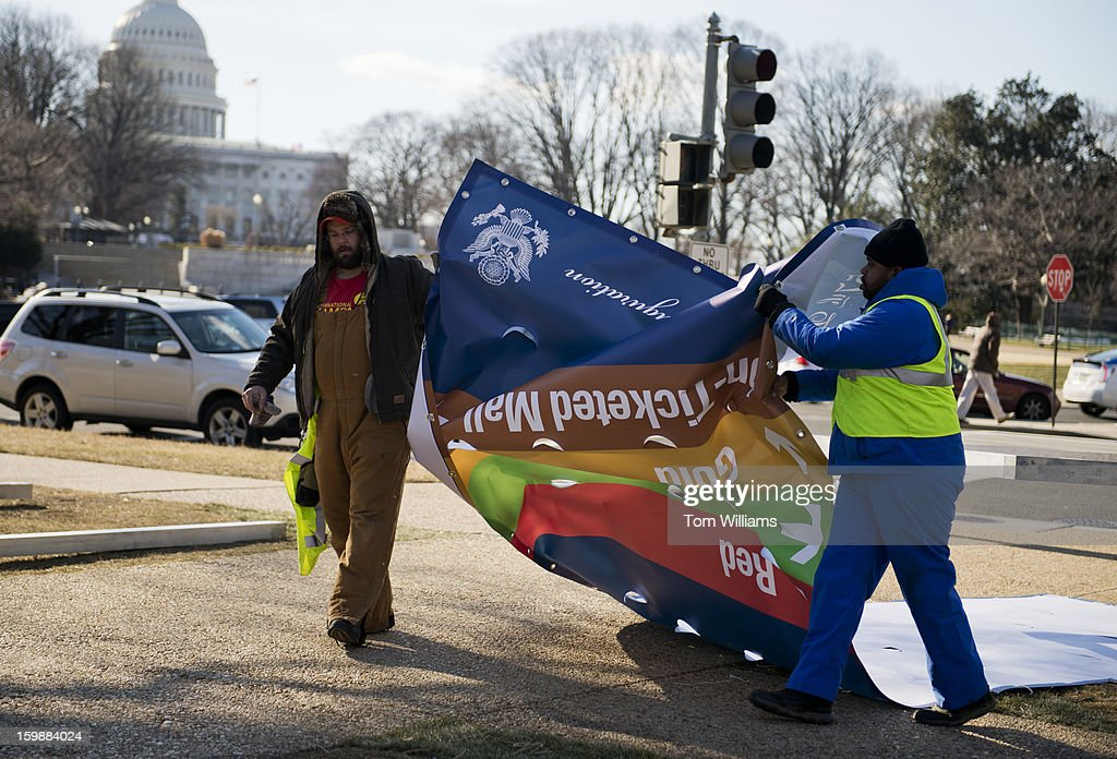 Workers pack up signs along Louisiana Avenue, that helped guide attendees of yesterday's 57th presidential inauguration of President Barack Obama.