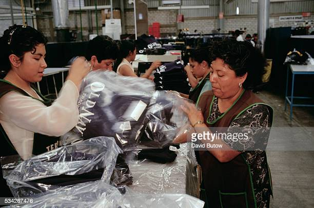 Workers package finished Old Navy sweatshirts at the Qualytel de Puebla clothing manufacturing plant in Puebla Mexico Qualytel produces garments for...