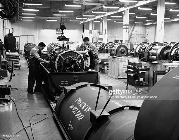 Workers package General Electric's J47 jet engines in air tight and water proof containers in the shipping room These engines are delivered to...