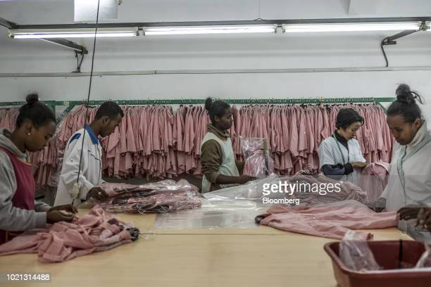 Workers package men's shirts at a textile manufacturing facility in Antananarivo Madagascar on Wednesday July 25 2018 Madagascar's exports are...