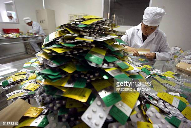 Workers package pills at Guilin Pharmaceutical one of only two Chinese companies converting what was formerly considered wild grass herbs into raw...