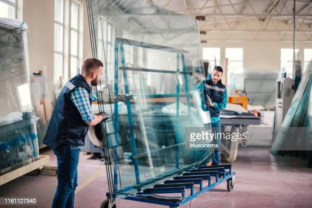lavoratori che confezionano lastre di vetro in magazzino - vetro foto e immagini stock