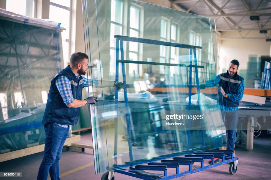 Workers packaging glass sheets in warehouse : Stock Photo