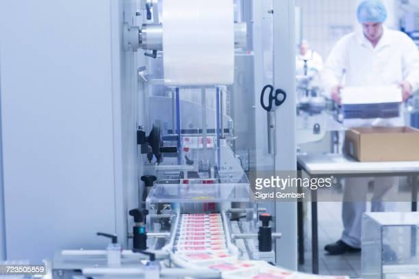 workers packaging pharmaceutical products on production line in pharmaceutical plant - sigrid gombert stockfoto's en -beelden